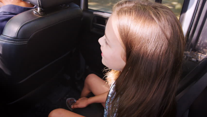 Young girl travelling in the back of a car with grandparents
