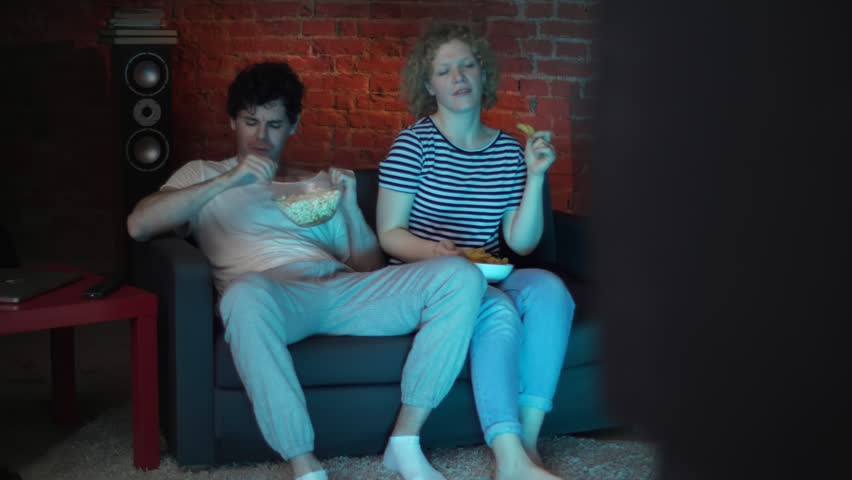 Positive couple of lovers - man and woman are sitting on the couch watching a music video clip and dancing at home in a private penthouse