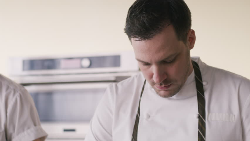 Close up of chefs cooking in kitchen restaurant together. Restaurant cinematic scene.