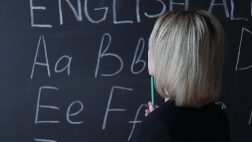 Teacher is writing letter of alphabet on blackboard with chalk. Education in elementary school concept.