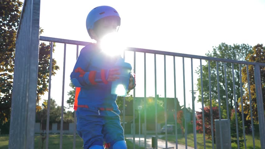 small boy drinks refreshing beverage from plastic container outdoors in backlight close-up