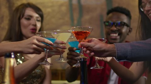 Close up shot of joyful young people sitting in cafe or bar and clinking martini glasses with colored alcoholic cocktail in them