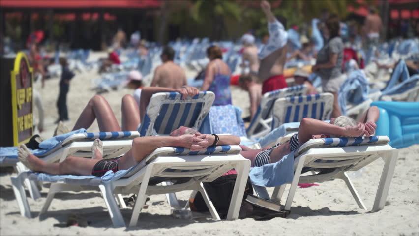 Tourists sunbathing and enjoying the summer in a beach. Crowded tropical beach - March 2018: Labadee Island, Haiti