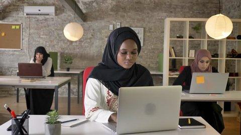 Young black muslim women in hijab working on laptop and yawning, sleepy, three beautiful muslim womens sitting in modern office