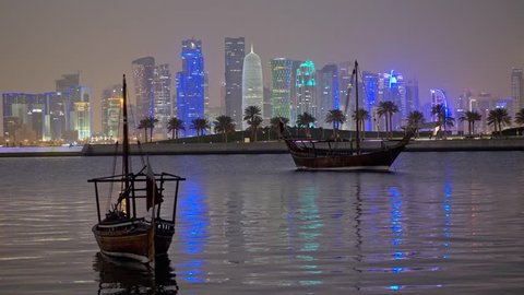 Skyline of Doha, Qatar with Traditional Arabic Dhow boats at night.