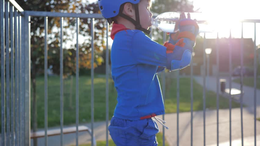 thirst quenching, kid drinks mineral water from plastic bottle at Skate Park in sunlight