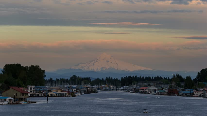 Time lapse video of moving clouds over snow covered mt. hood and Columbia river gorge with residential boathouses in Hayden Island 4k uhd