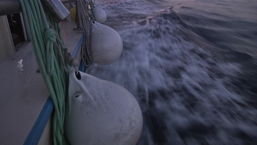 Close up of buoys hanging off the side of a boat as it speeds through the water