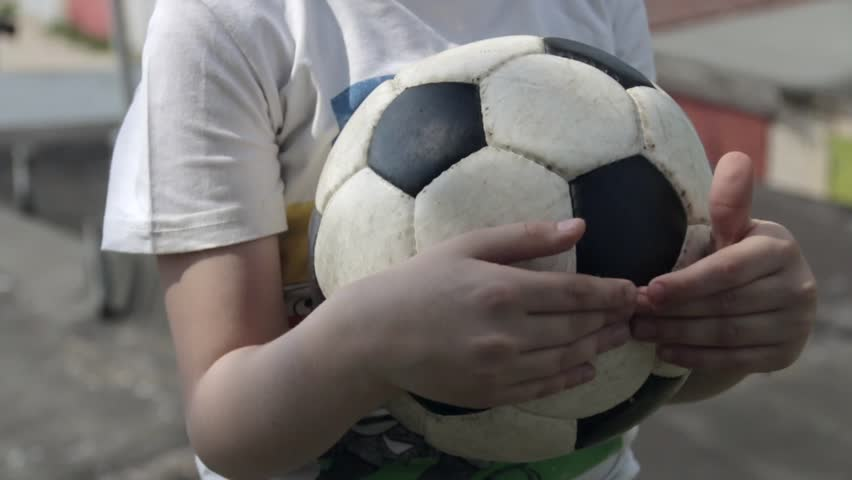 Young white boy holds a soccer ball in his hands in outdoor   Shutterstock HD Video #1012604873
