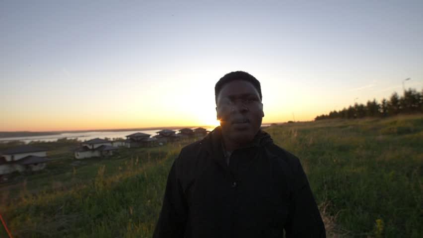 Young african man smoking in summer evening field at beautiful sunset | Shutterstock HD Video #1012671773