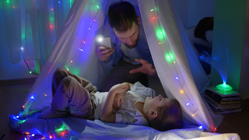 Family fun, father tickling toddler in children tent with vivid lights at night in weekend | Shutterstock HD Video #1012674083