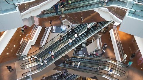 Time lapse escalators in modern shopping mall crowd of people. Very busy full of clients mall complex. Consumption concept