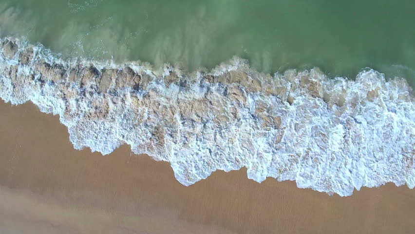 Up above the waves then zooming in drone shot on Canaveral national seashore also known as New Smyrna beach in the summer 2018 | Shutterstock HD Video #1012691903