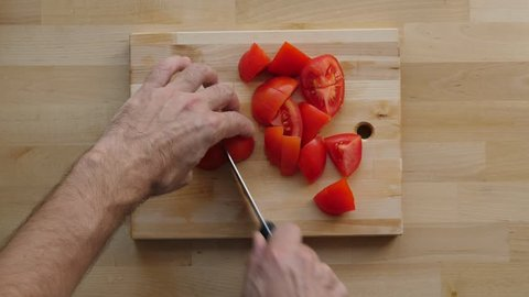 Man cut tomato to cloves on wooden board at kitchen table, overhead shot. Two middle sized ripe tomatoes lie in four half pieces. Chief take them and slice to smaller pieces, prepare vegetarian meal