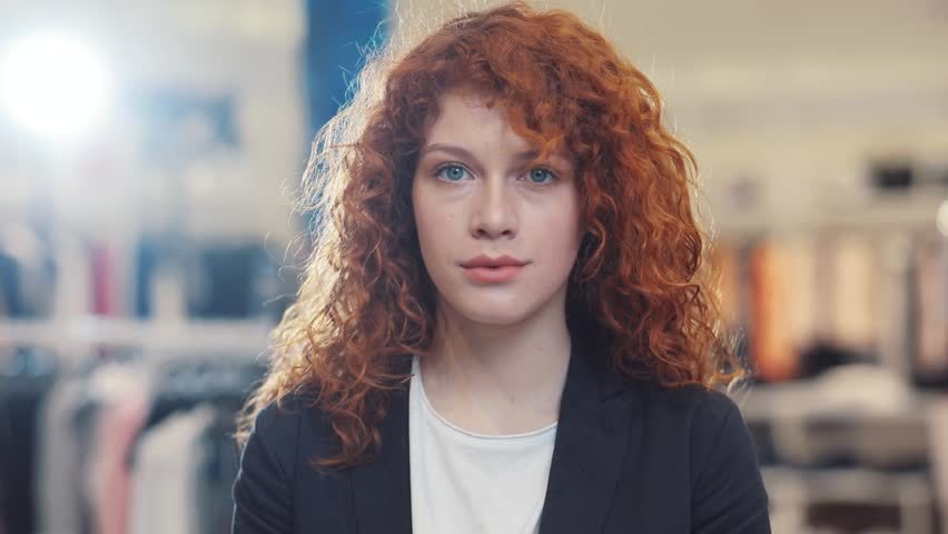 Portrait of red curly hair young woman look at camera at clothes store design girl shopping face spring customer light happy indoors female retail beautiful lifestyle pretty young adult cute lady | Shutterstock HD Video #1012720193