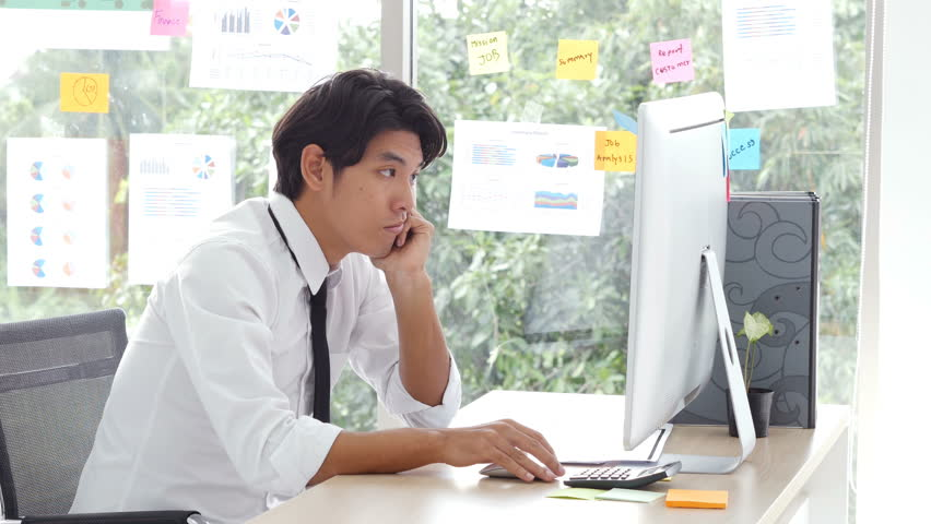 Businessman boring when he work at office. Bored asian male office worker struggles to stay awake at his desk.