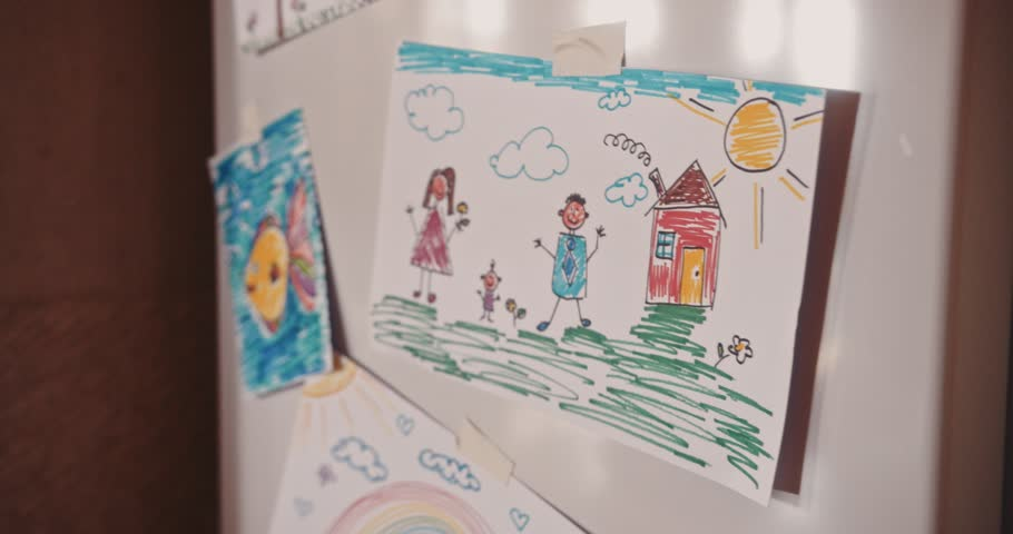 Kid's drawings showing mother, father and child placed on fridge door in family house kitchen
