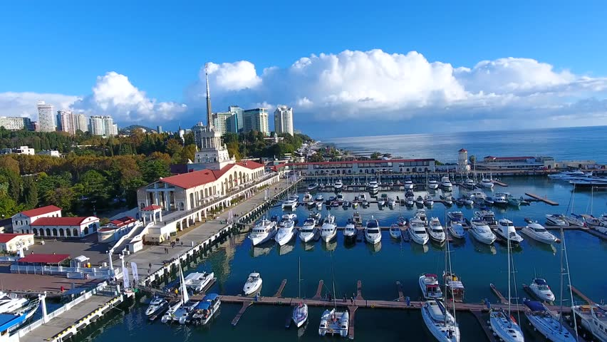 A beautiful summer Aerial Flight over the city of Sochi and a seaport early in the morning 4k