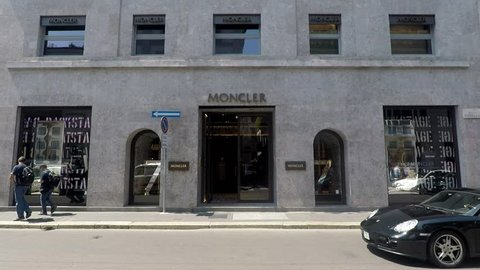 Milan, Italy - June 21 2018 : Via Montenapoleone, the Moncler fashion shop with Porsche car passing by