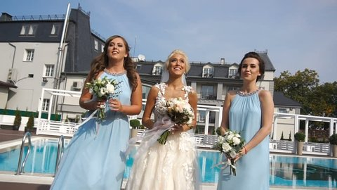 Gorgeous smiling blonde bride and her pretty bridesmaids are throwing in the air wedding bouquets and catching them near the swimming pool.