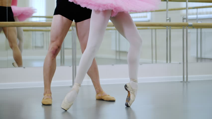 Legs close up. Rehearsal in the ballet hall or studio with minimalism interior. Young professional sensual dancer's couple in comfortable clothing dancing together. Slow motion. | Shutterstock HD Video #1012770443
