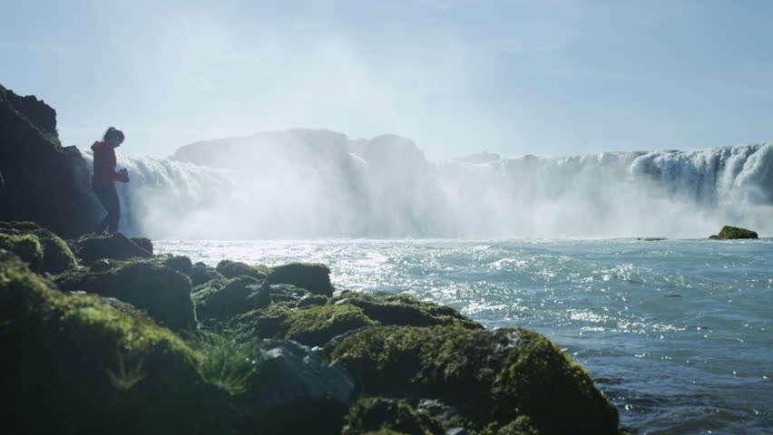 Woman taking photos of Godafoss waterfall in Iceland | Shutterstock HD Video #1012772753