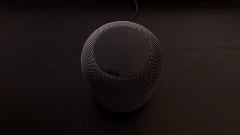 Ostfildern, Germany - June 25, 2018: Using an Apple HomePod speaker - the smart speaker is reacting to voice input and signalling its attention by the changing lights