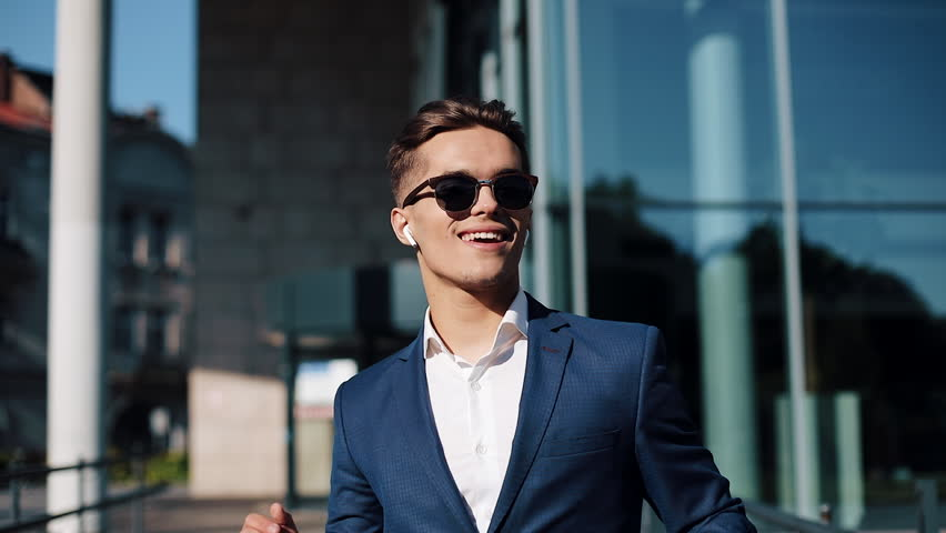 Young businessman with sunglasses listening to the music on his smartphone outdoors and dancing. He walking near office building. Communication, audiobooks, music, business people. Shot on Red Epic