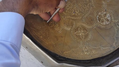 craftsman engraving patterns on the tray. masters of Central Asia and Uzbekistan. manual copper minting. the old art of etching on utensils