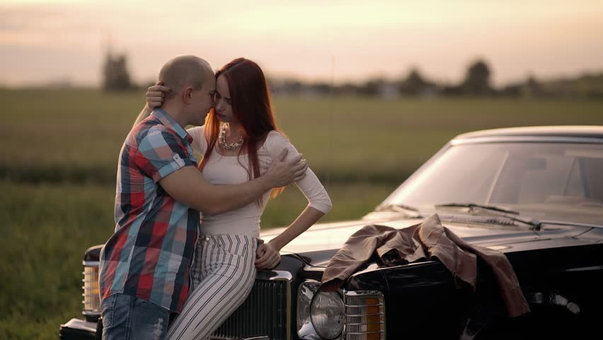 Couple hugging and kissing in nature near a retro car