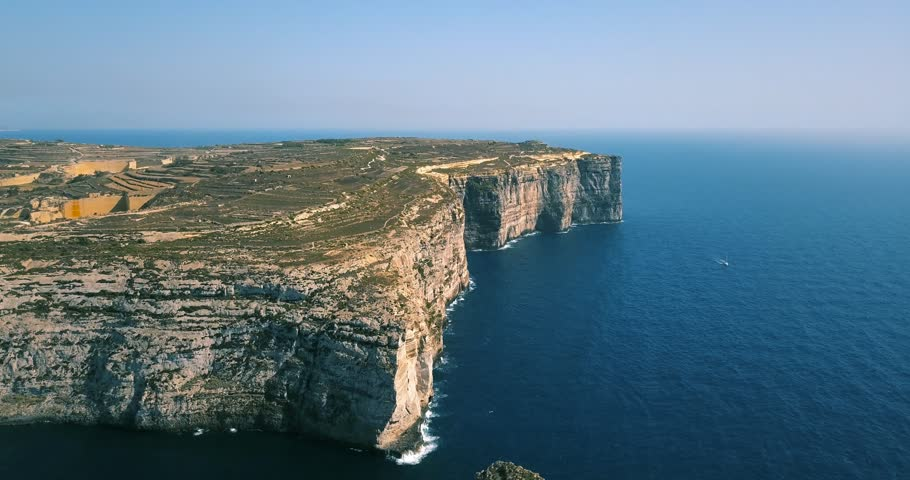 Scenic aerial view of dramatic high precipice with beautiful sea view. Yacht sailing boat in the sea. Drone top view shot of dangerous stony cliffs. Gozo island, Malta