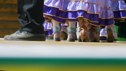 Legs of ladies in folk national tatar leather boots and long skirts walks on stage