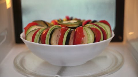 Using microwave for cooking vegetables. Making ratatouille in microwave. Bowl with sliced fresh raw veggies steaming inside oven.