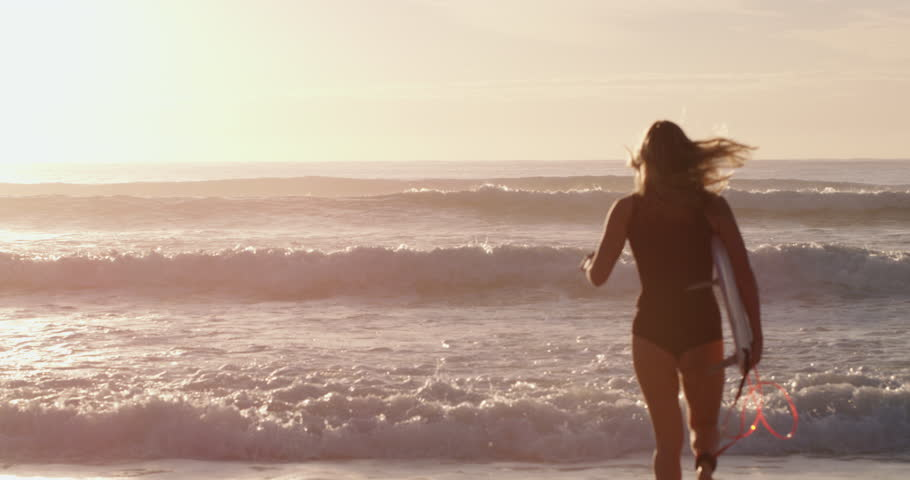 Attractive female surfer running into the ocean waves with her surfboard at sunset. Shot with a RED camera. 4k footage.