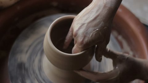 creation of ceramic products. Artisan makes cup from wet clay at potter's wheel