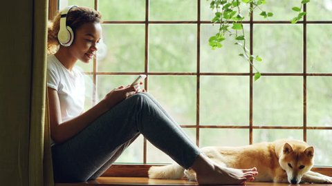 Attractive young woman is listening to music through wireless headphones and choosing song on smartphone, her pet dog is lying on windowsill near its owner.