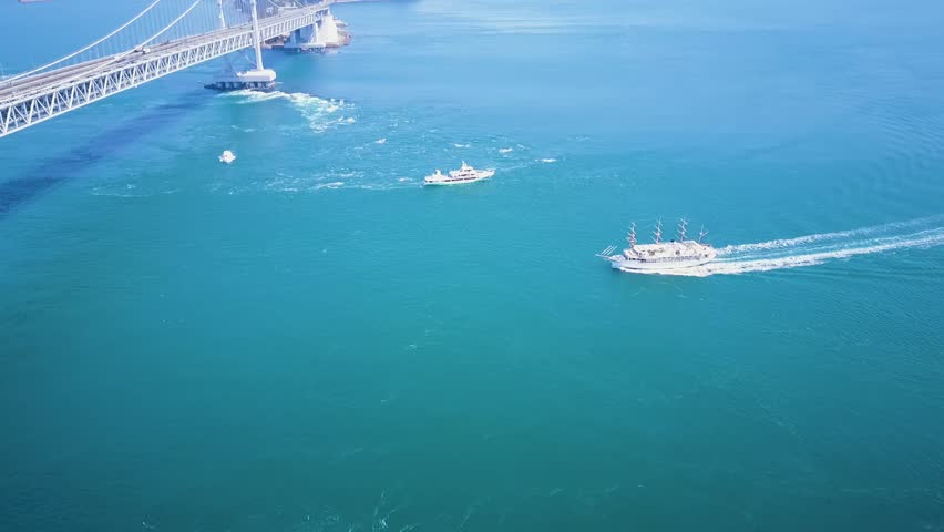Naruto bridge, whirlpool viewing boats travel below ferrying tourists in Tokushima Japan.