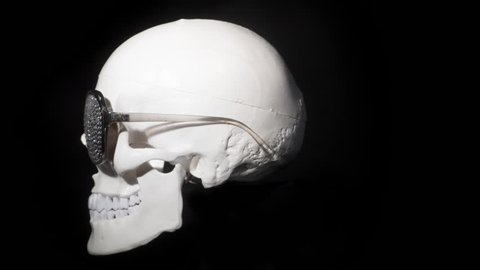 skull rotating against black with sparkling sunglasses.