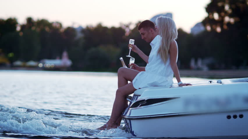 Beautiful young couple drinking champagne on floating boat. Love story concept. Luxury outdoors vacation on powerboat. Romantic date on river in evening. Love couple relaxing on floating yacht