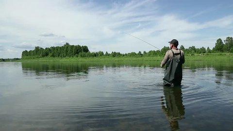 Joyful fisherman is fishing in calm river water near the shore