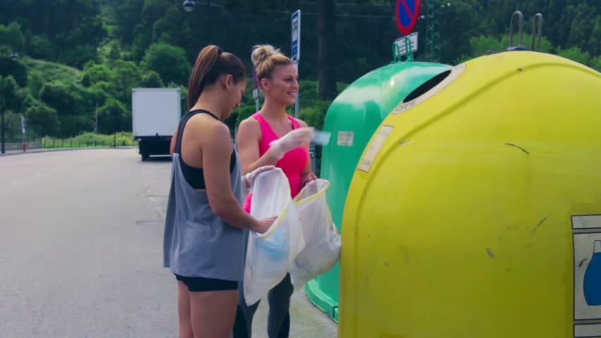Two girls throwing garbage to recycling dumpster after plogging