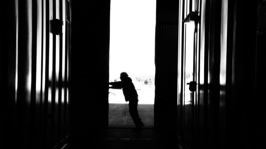 Warehouse Worker Pushing Metal Door. Black and White Tone. Zoom In. | Shutterstock HD Video #1012982843