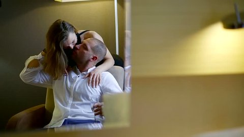 Handsome bald man in suit gently kisses woman's neck in a hotel room.