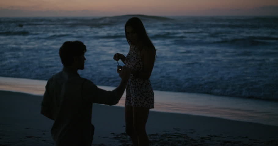 Young man taking photo of girlfriend holding sparklers dancing using smartphone celebrating new years eve laughing playful together on beach at sunset | Shutterstock HD Video #1012995203