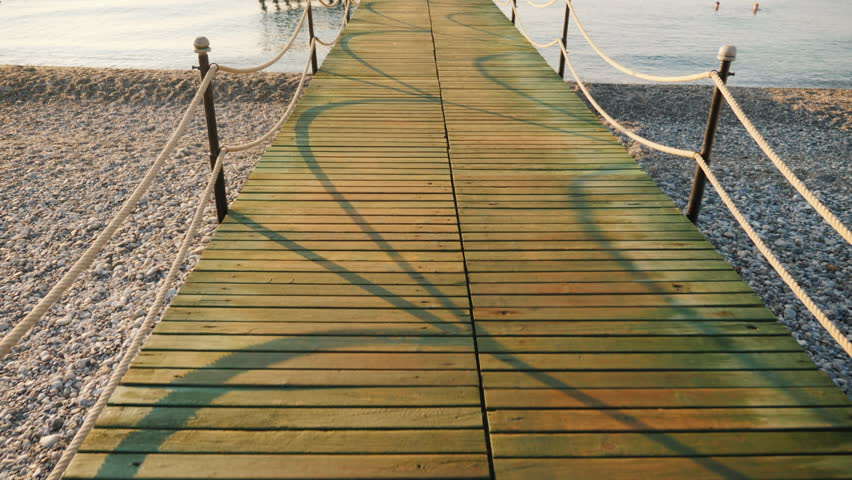 Walk on a wooden pier to the sea, a first-person view | Shutterstock HD Video #1012996013