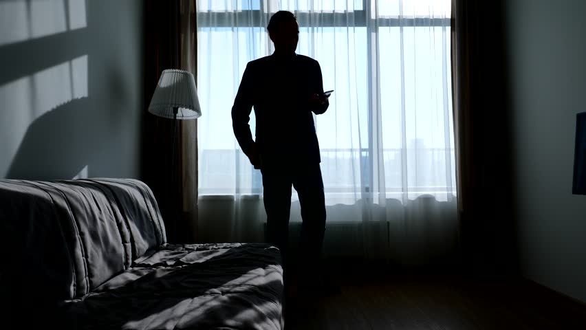 Busy guy wearing casual suit talk on phone and check other smartphone, walk against living room window. Silhouetted shot, bright sun light shine from outside   Shutterstock HD Video #1013008343
