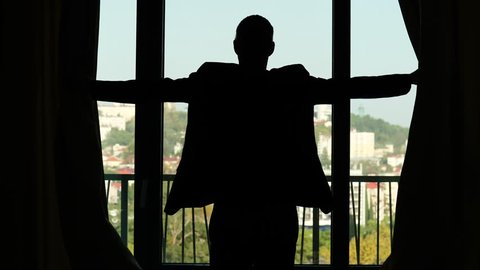 Man open curtains at midday, stay against window and look to sunny city view from high floor. Black silhouette, half length view from back