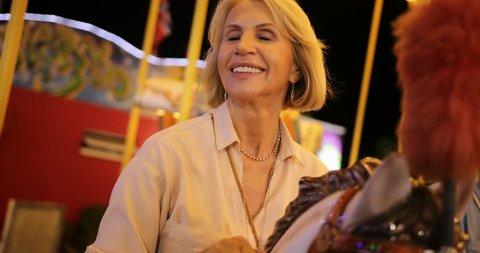Happy mature women riding carousel horses and enjoying amusement park merry-go-round ride on summer holidays
