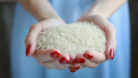 Caucasian female model pouring white rice from the palm of her hands. Shot in 4K
