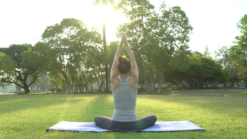 Young asian woman yoga outdoors keep calm and meditates while practicing yoga to explore the inner peace. Yoga and meditation have good benefits for health. Yoga Sport and Healthy lifestyle concept. | Shutterstock HD Video #1013080853